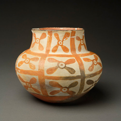 This is a stunning small jar from Laguna Pueblo.  It is 8″ tall by 8 1/2″ in diameter.  The rim is black and there is a double framing line between the mid-body and base. The design features a checkerboard motif with butterflies(?), flowers(?), propellers(?); well, your guess is as good as mine.  What is wonderful is the pure orange as the all over dominant color.  The natural outdoor firing allowed this color to emerge over most of the pot and it is absolutely striking and distinctive.  There is a lovely fire cloud on the base, a testament to traditional firing and some orange paint spillage just inside the rim, which is delightful. Condition is very good, no cracks or repairs or chips that I can find.  There is some spalling from age and possibly water use, but it does not at all attract from this jars' lovely appearance; so I have chosen not to have it restored.  So it is in original condition. I admit it; I love this jar!
